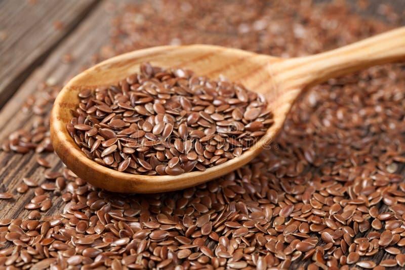 Montón de las semillas de lino en cuchara de madera del vintage foto de archivo