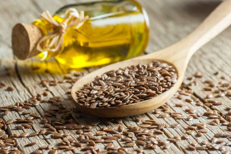 Montón de las semillas de lino o de las linazas en cuchara con el vidrio de aceite de linaza en el contexto de madera imagenes de archivo