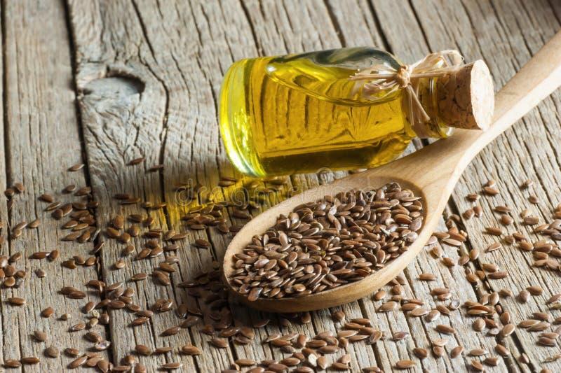 Montón de las semillas de lino o de las linazas en cuchara con el vidrio de aceite de linaza en el contexto de madera fotografía de archivo libre de regalías