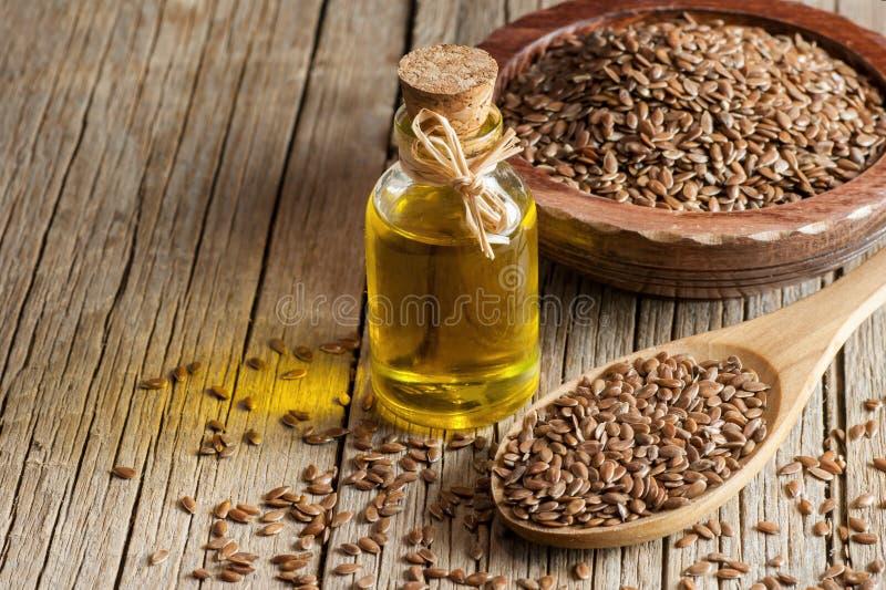 Montón de las semillas de lino o de las linazas en cuchara y cuenco con el vidrio de aceite de linaza en el contexto de madera fotografía de archivo