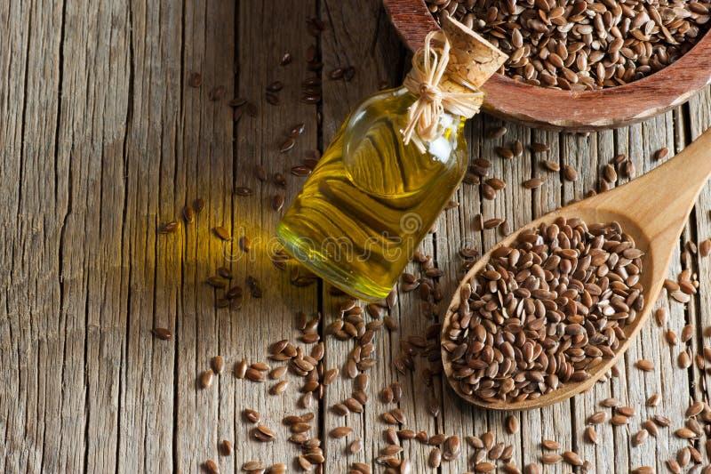 Montón de las semillas de lino o de las linazas en cuchara y cuenco con el vidrio de aceite de linaza en el contexto de madera fotos de archivo libres de regalías