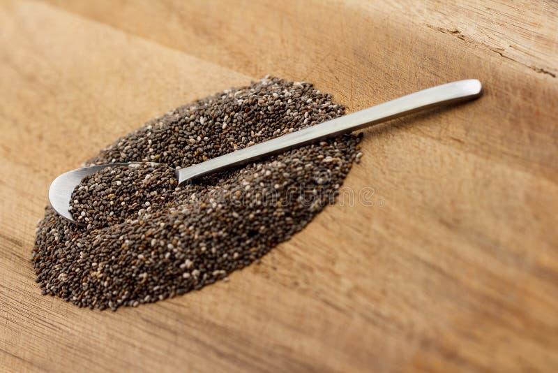 Montón de las semillas y de la cuchara del chia en la madera foto de archivo libre de regalías