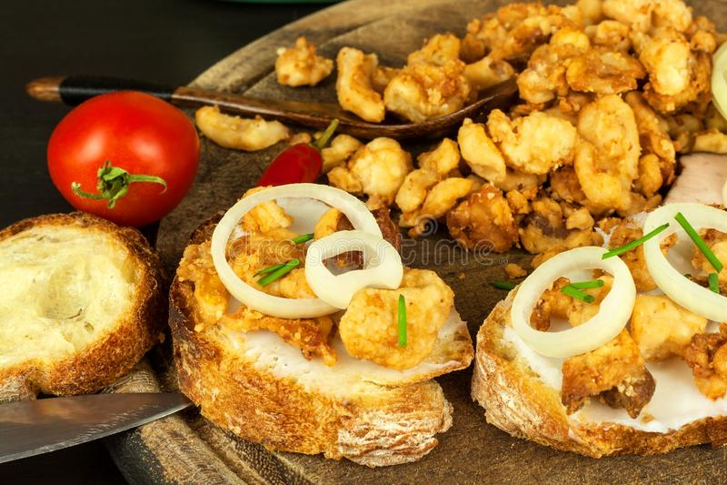 Montón de los chicharrones fritos salados nacionales del cerdo Comida basura grasa Chicharrones del cerdo en el tablero de la coc imágenes de archivo libres de regalías