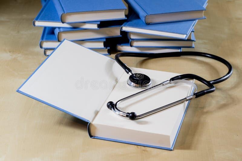 Montón de los libros que leen en una tabla de madera Al lado de mentiras y de stethos foto de archivo