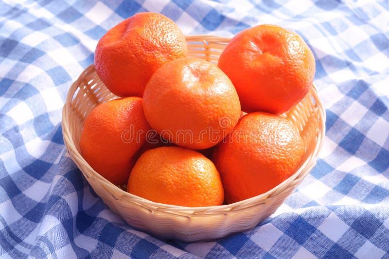Montón de los mandarines frescos de las mandarinas en cesta de mimbre en servilleta del mantel fotografía de archivo libre de regalías