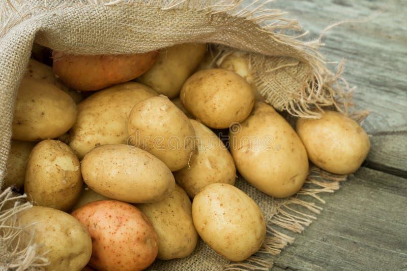 Montón de patatas jovenes en bolso de la harpillera imagenes de archivo