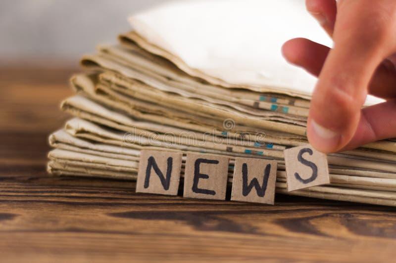 Montón de periódicos viejos al lado de cuadrados humanos del rectángulo de la mano y de la cartulina con noticias manuscritas de  foto de archivo libre de regalías