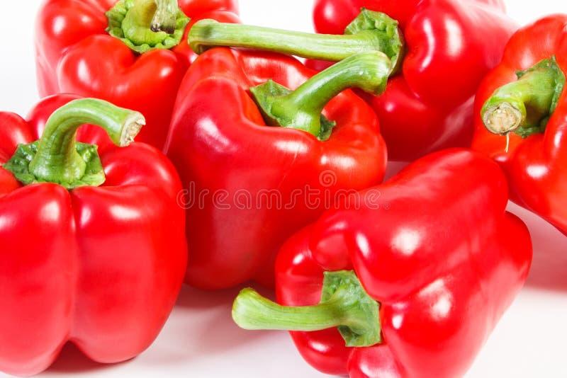 Montón de pimientas maduras rojas en el fondo blanco, nutrición sana imagen de archivo