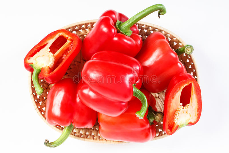 Montón de pimientas rojas en cesta de mimbre en el fondo blanco, concepto de nutrición sana imagenes de archivo