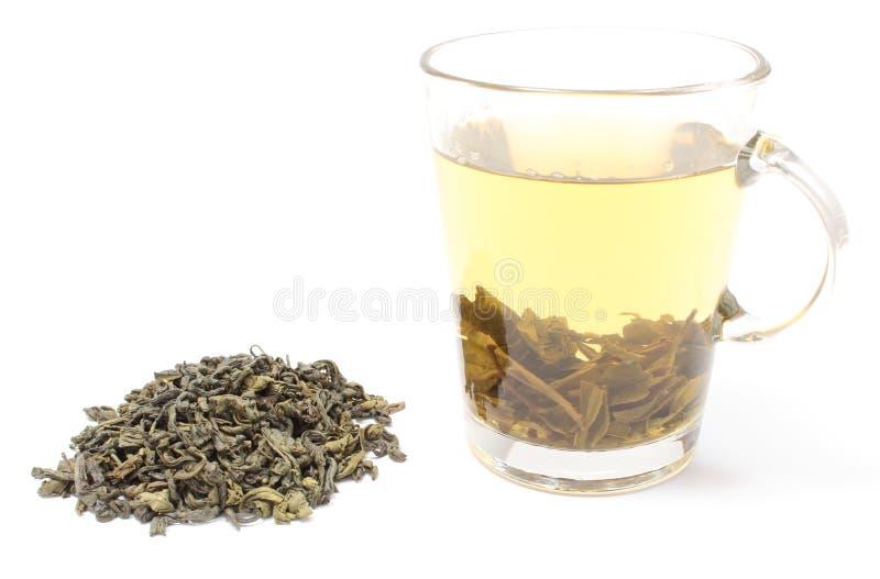 Montón del té verde y taza de bebida. Fondo blanco imagen de archivo libre de regalías