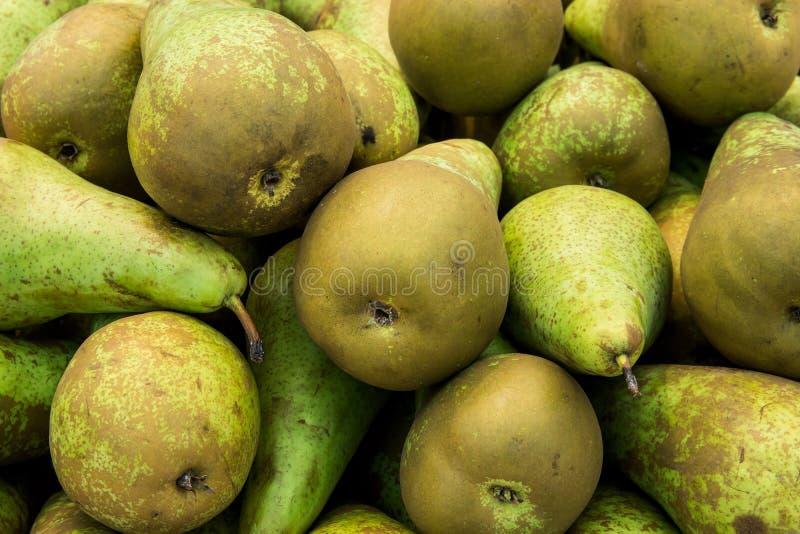 Montón del verde orgánico maduro y de las peras de la conferencia de Brown en el mercado de los granjeros Colores vivos vibrantes imagen de archivo libre de regalías