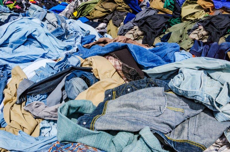 Montões da roupa no mercado de segunda mão fotografia de stock