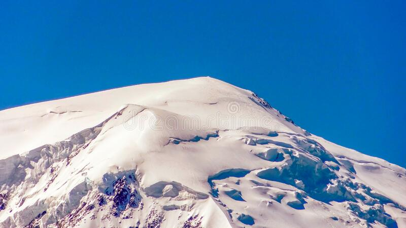 Mont Blanc is an array of high Alpine mountains in the French Alps. close - up of the peak against the blue sky stock images