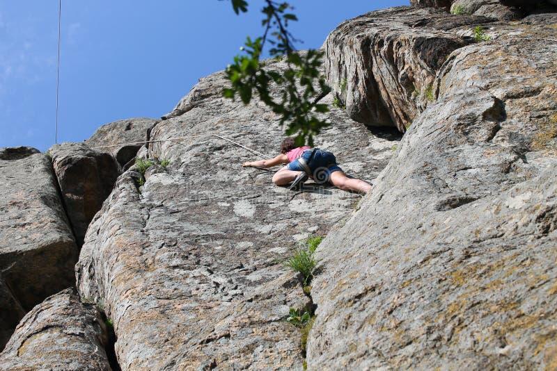 Mont?es de grimpeur de roche de fille sur la roche images stock