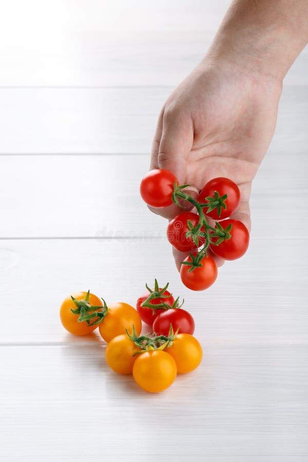 Mont?n de los peque?os tomates de cereza rojos y amarillos en la tabla blanca Copie el espacio fotos de archivo