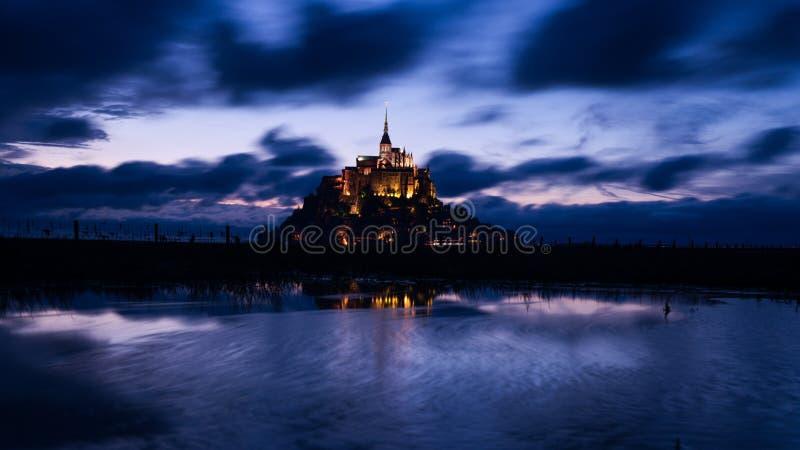 Mont Saint Michael con la riflessione dell'acqua durante l'immagine del centro di notte immagini stock