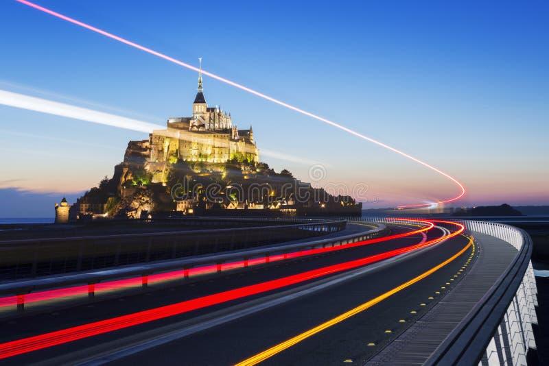 Mont Saint-Michel στο σούρουπο με το φως λεωφορείων στοκ εικόνες