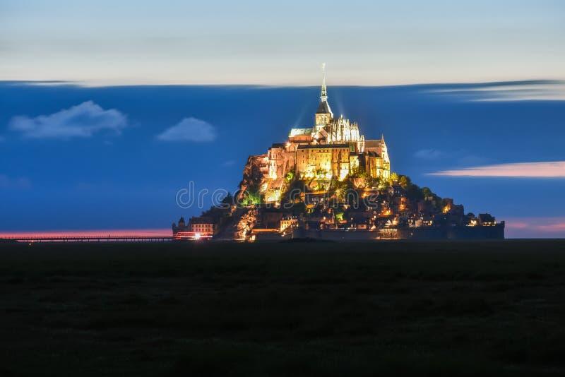 Mont Saint Michel illuminato al crepuscolo in un cielo colourful con le nuvole su estate, Francia immagine stock libera da diritti