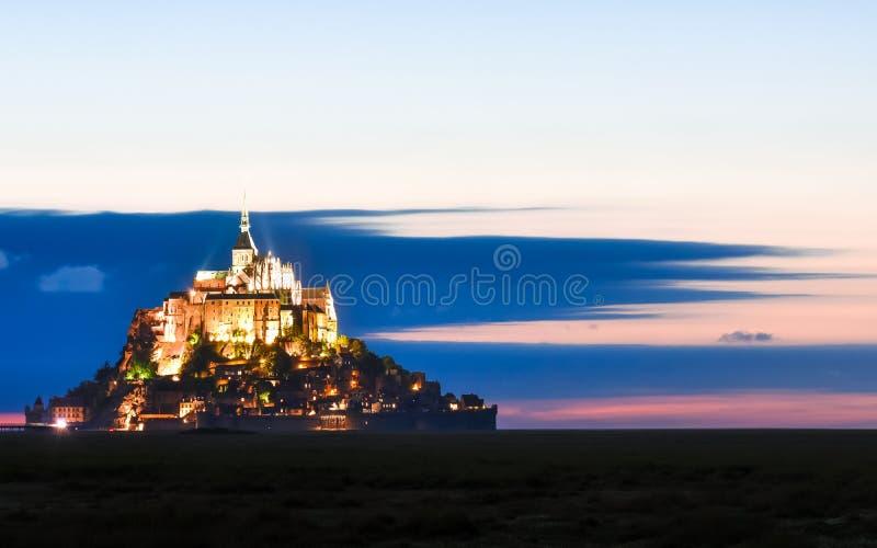 Mont Saint Michel lumineux au crépuscule dans un ciel coloré avec des nuages l'été, France photo stock