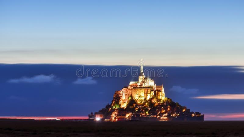 Mont Saint Michel lumineux au crépuscule dans un ciel coloré avec des nuages l'été, France photos libres de droits
