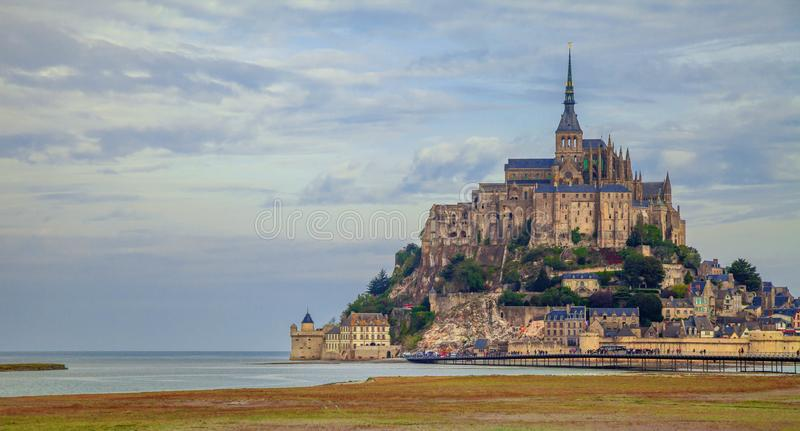 Mont Saint-Michel in Normandy France across the mudflats. View across marshland and mudflats in St Michael`s bay towards Mont Saint Michel Northern France stock images