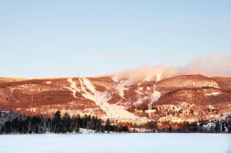MONT-TREMBLANT, QUEBEC, KANADA - 28 2017 GRUDZIEŃ: Zima krajobraz ośrodek narciarski z Zamarzniętym jeziorem, Narciarskimi skłona fotografia stock