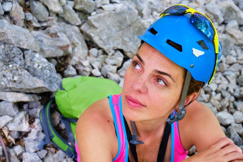 Montañés de la mujer con el casco y mochila, sentándose, descansando y mirando para arriba hacia una pared de la escalada fotografía de archivo