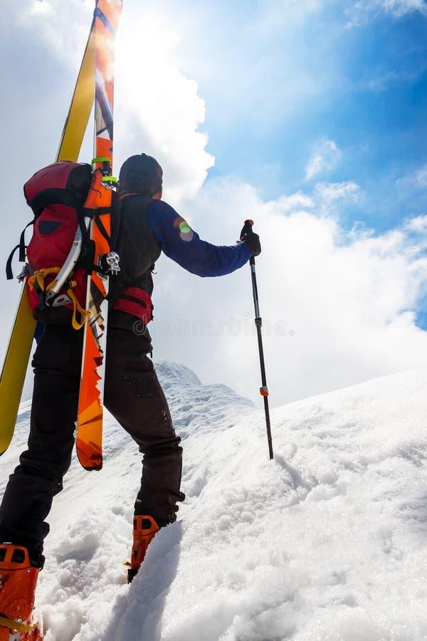 Montañés del esquí que camina para arriba a lo largo de un canto nevoso escarpado con el s foto de archivo