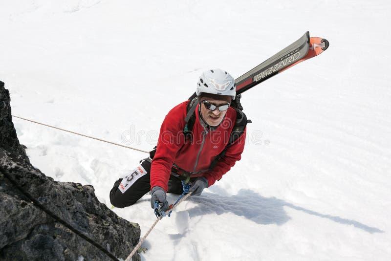 Montañés del esquí que sube en cuerda en la montaña rocosa imagen de archivo libre de regalías