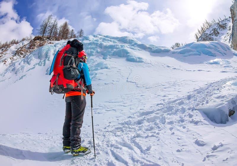 Montañés femenino con la mochila, el casco y el arnés con subir en montaña imagenes de archivo