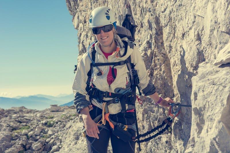 Montañés femenino feliz que sube vía ferrata imagen de archivo