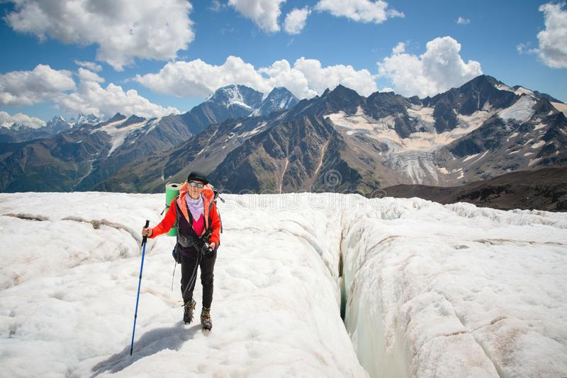 Montañés femenino que disfruta de la belleza de los paseos del glaciar en el glaciar en el grampón y las gafas de sol Contra fotografía de archivo libre de regalías