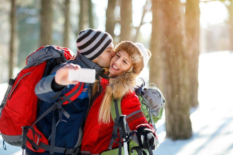 Montañés masculino que besa a su novia mientras que hace el selfie en w imágenes de archivo libres de regalías