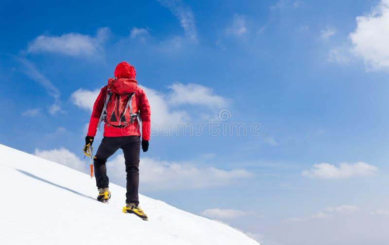 Montañés que camina cuesta arriba a lo largo de una cuesta nevosa. fotos de archivo libres de regalías