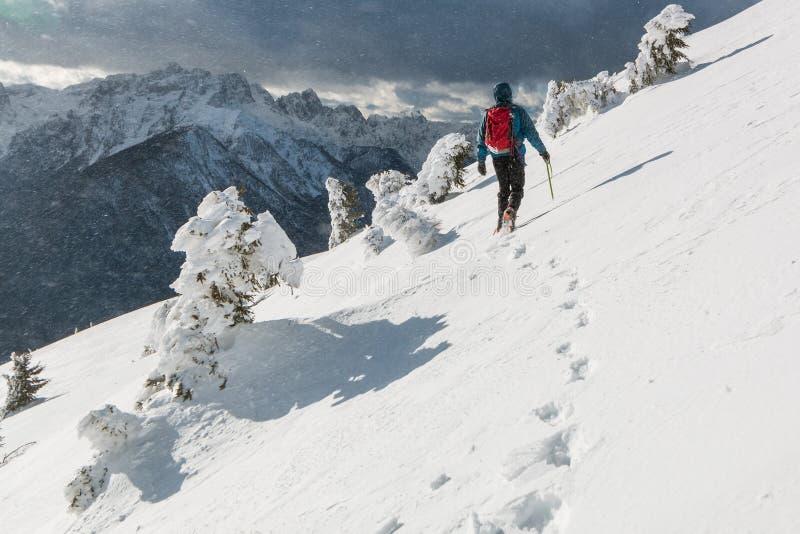 Montañés que camina en la cuesta nevosa foto de archivo