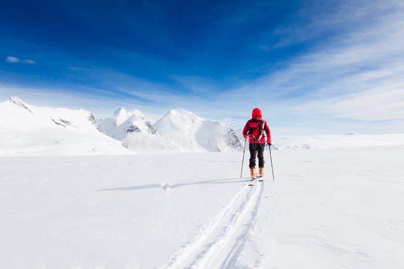 Montañés que camina en un glaciar durante un invierno a gran altitud e foto de archivo