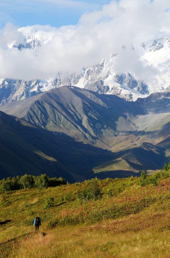 Montañés que sigue la ruta famosa del senderismo en las montañas del Cáucaso imagenes de archivo