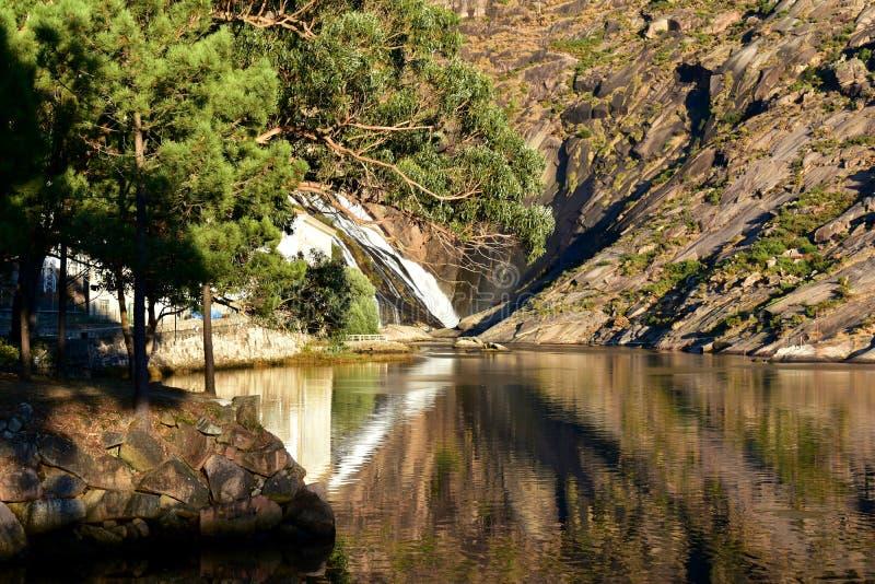 Montaña, árboles, río y cascada con reflexiones del agua y luz de la puesta del sol Ezaro, Galicia, España imágenes de archivo libres de regalías