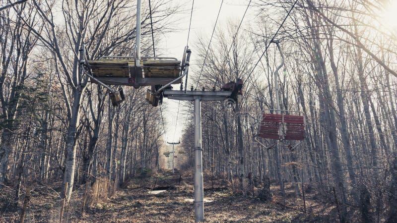 Montaña abandonada Ski Lift en el bosque con las sillas de madera imagen de archivo