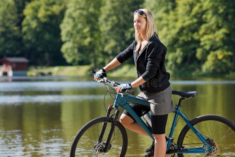 Montaña biking el lago que hace una pausa de la mujer joven imagen de archivo