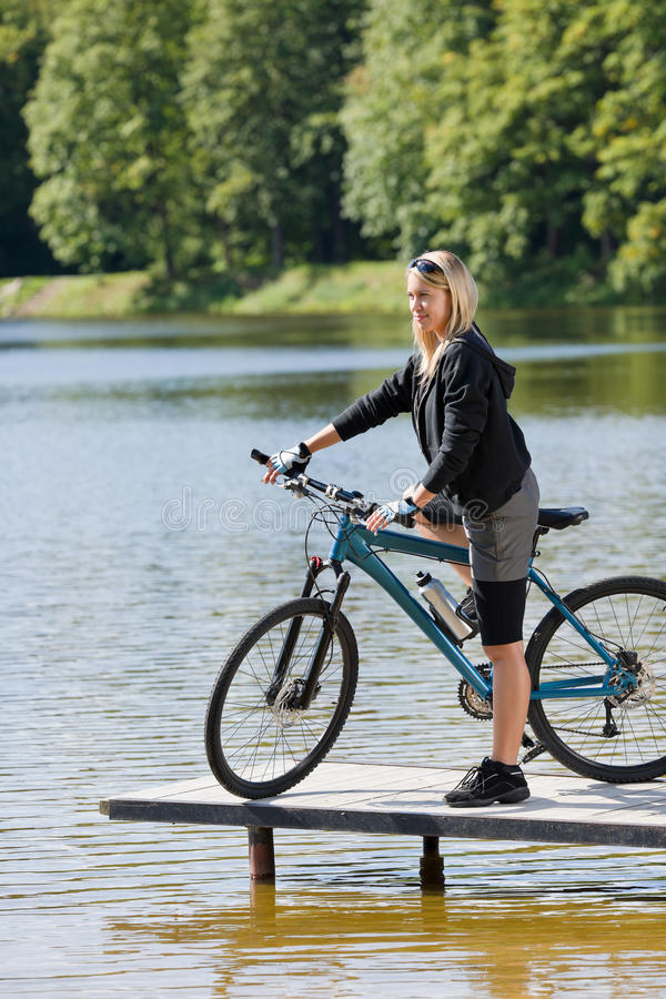 Montaña biking el lago que hace una pausa de la mujer joven imágenes de archivo libres de regalías
