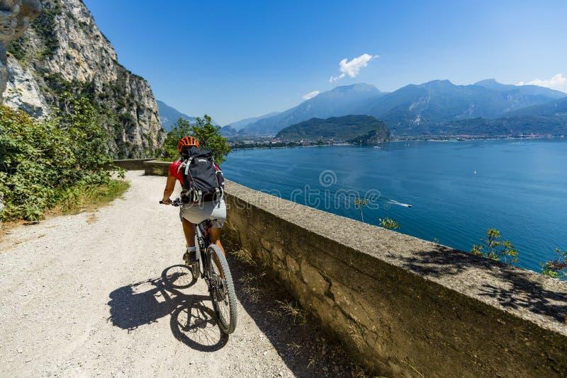 Montaña biking en la mujer de la salida del sol sobre el lago Garda en la trayectoria Sentier foto de archivo