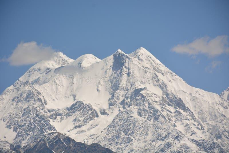 montaña con la nieve y las nubes blancas imagen de archivo