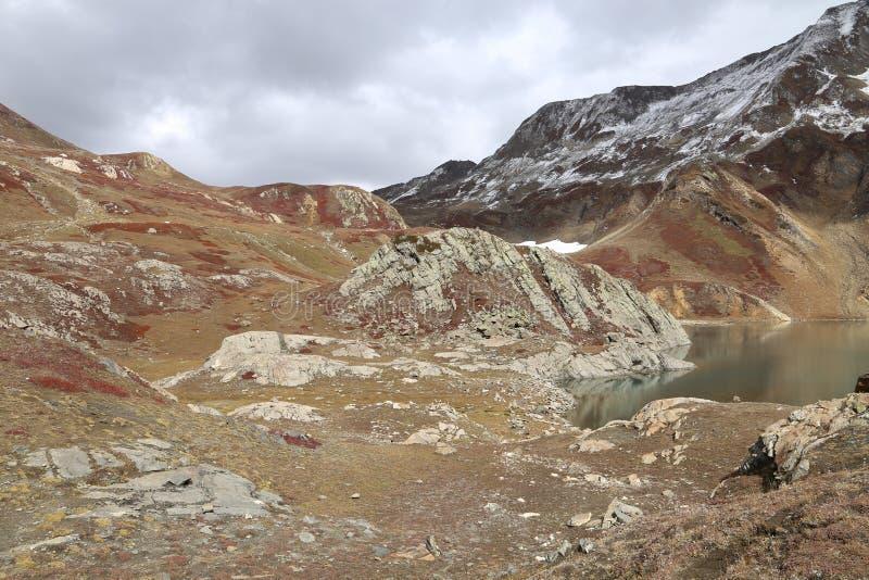 Montaña cubierta por el glaciar y la vista del lago que sorprende debajo de las nubes oscuras imagenes de archivo