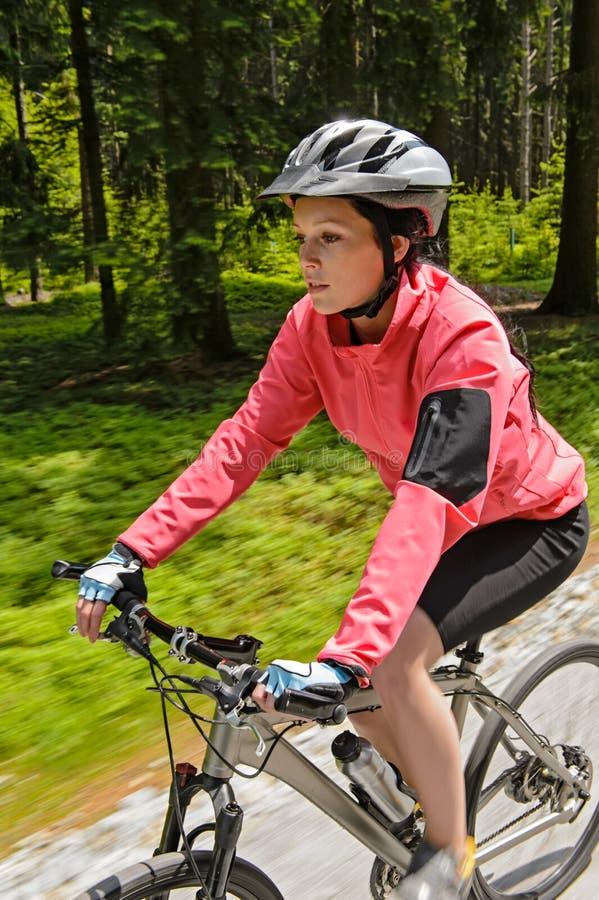 Montaña de la mujer biking en la falta de definición de movimiento del bosque foto de archivo libre de regalías