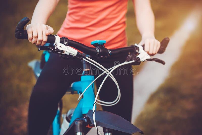 Montaña de la mujer biking y que sostiene los manillares fotos de archivo