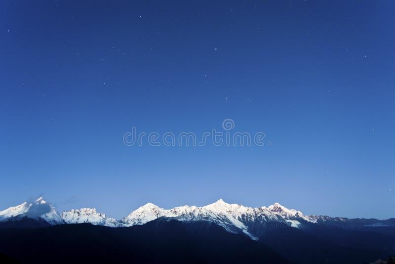 Montaña de la nieve en el amanecer con las estrellas imagen de archivo libre de regalías