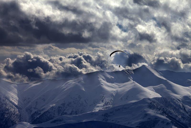Montaña de la tarde con las nubes y la silueta del paracaidista imagenes de archivo