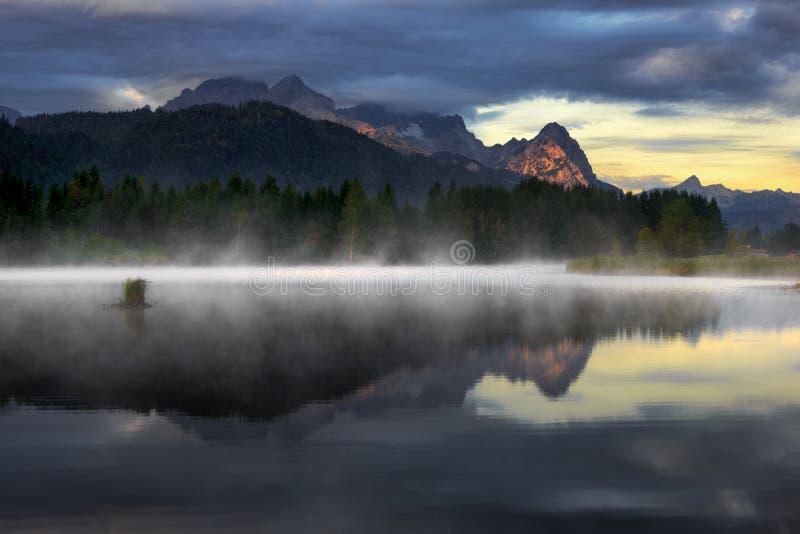 Montaña de Wetterstein durante día del otoño con niebla de la mañana sobre el lago Geroldsee, montañas bávaras, Baviera, Alemania fotos de archivo libres de regalías