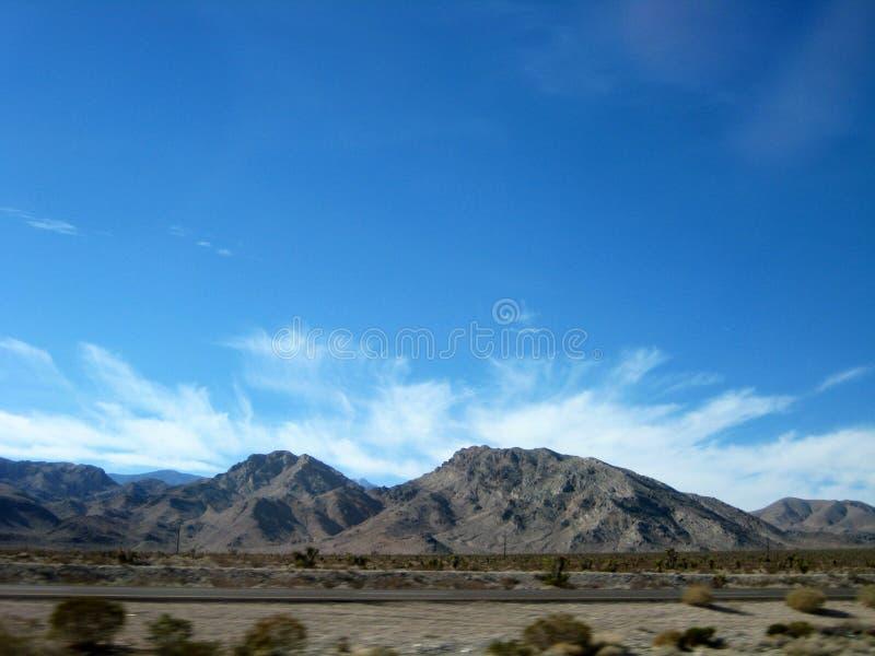 Montaña del desierto debajo del cielo azul y de rayar las nubes blancas fotos de archivo libres de regalías